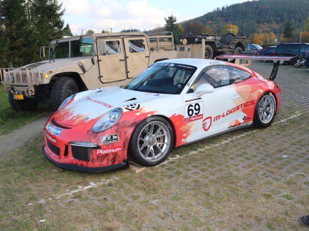 Wyścigówka Porsche należące do Lukas Motosport, w tle maszyny Bredy