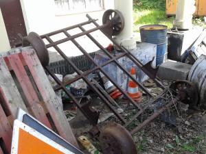 Wózek szynowy dogorywa wśród innego złomu